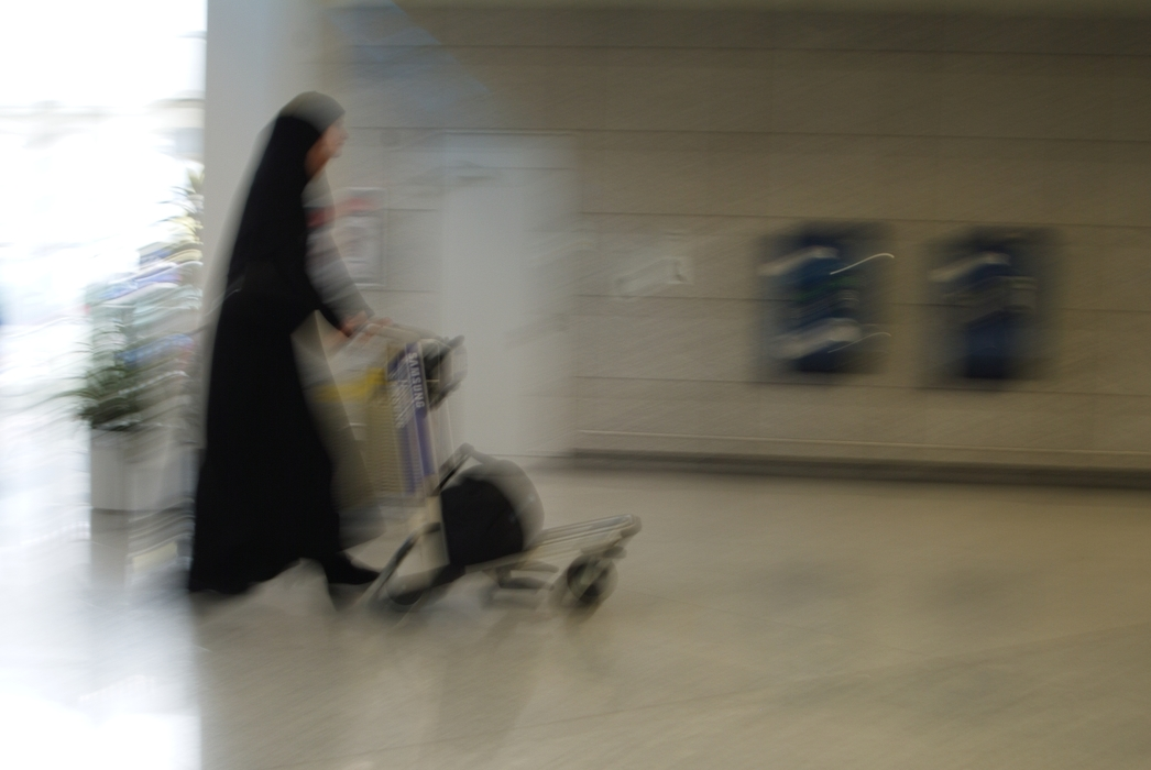 Woman Walking with Luggage Cart