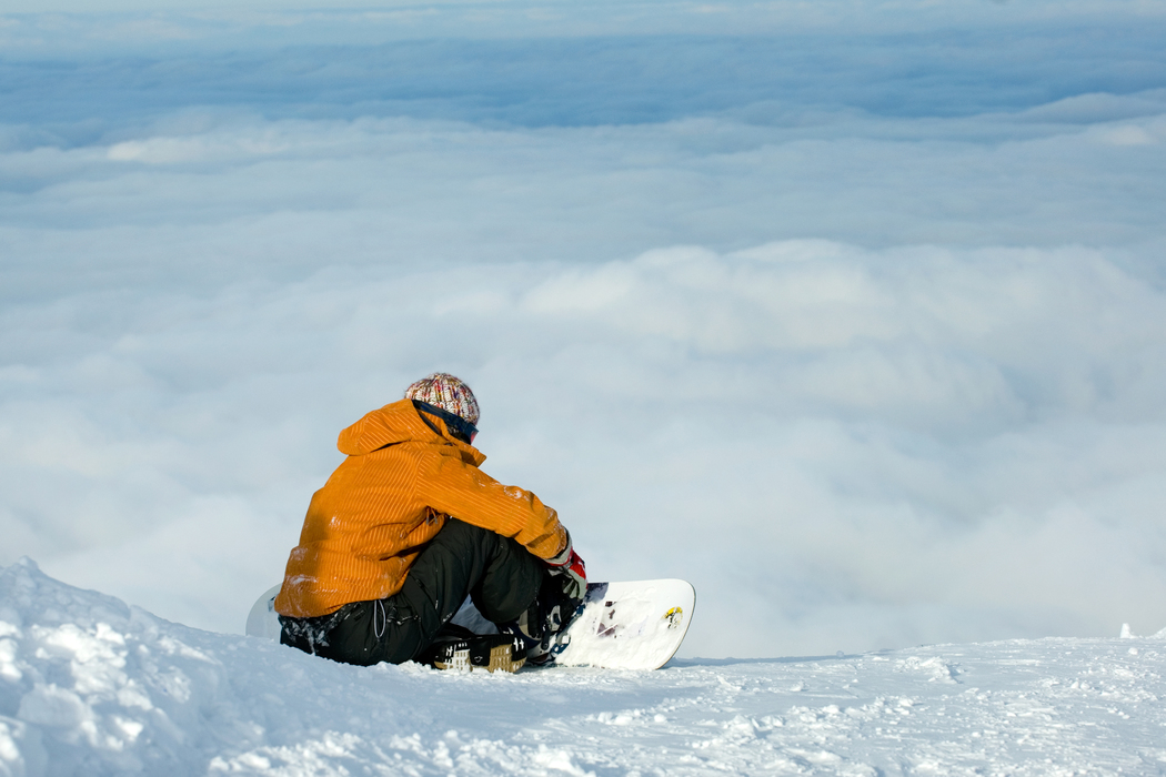 Snowboarder siting on snow